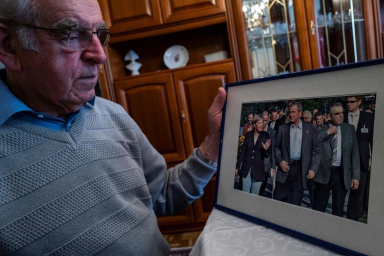 Wolfhard Molkentin, ancien responsable local de la CDU, montre une photo prise en 2007 d'Angela Merkel (g), du président américain George W. Bush (c) et de lui-même (d), lors d'une interview chez lui, le 18 septembre 2021 à Grammendorf, en Allemagne