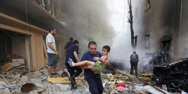 FOR USE AS DESIRED, YEAR END PHOTOS - FILE - In this Oct. 19, 2012 file photo, a Lebanese rescue man, carries an injured boy at the scene of an explosion in the mostly Christian neighborhood of Achrafiyeh, Beirut, Lebanon. A car bomb ripped through eastern Beirut, shearing the balconies of off residential buildings and sending bloodied victims pouring out into the streets in the most serious blast this city has seen in years. (AP Photo/Hussein Malla, File) Associated Press / Reporters