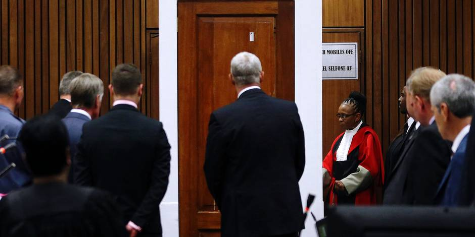 File: In this Friday, May 9, 2014 file photo Judge Thokozile Masipa, to right of door in red cape, and her advocates examine the bullet-riddled toilet door up close during expert forensics evidence being given at the Oscar Pistorius murder trial in in Pretoria, South Africa. Judge Masipa is expected to announce her verdict after summing up Thursday and Friday in Pistorius' murder trail after scrutinizing evidence given by 37 witnesses in a court transcript running to thousands of pages in a drama that has played out over six months. (AP Photo/Themba Hadebe, Pool, File)