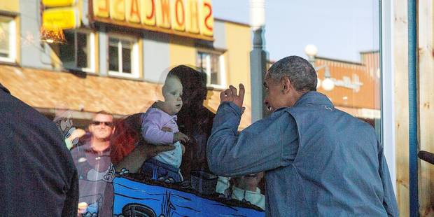 President Barack Obama greets a baby through a window in downtown Seward, Alaska, Tuesday, Sept. 1, 2015, after taking a hike to view the Exit Glacier. Obama is on a historic three-day trip to Alaska aimed at showing solidarity with a state often overlooked by Washington, while using its glorious but changing landscape as an urgent call to action on climate change. (AP Photo/Andrew Harnik)