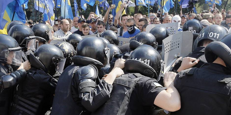 Flags of the of nationalist Svoboda (Freedom) party are seen in the background as police clash with protesters, after a vote to give greater powers to the east in front of the Parliament, in Kiev, Ukraine, Monday, Aug. 31, 2015. The Ukrainian parliament has given preliminary approval to a controversial constitutional amendment that would provide greater powers to separatist regions in the east. Hundreds of people gathered in front of the parliament to protest against the amendment. (AP Photo/Efrem Lukatsky)