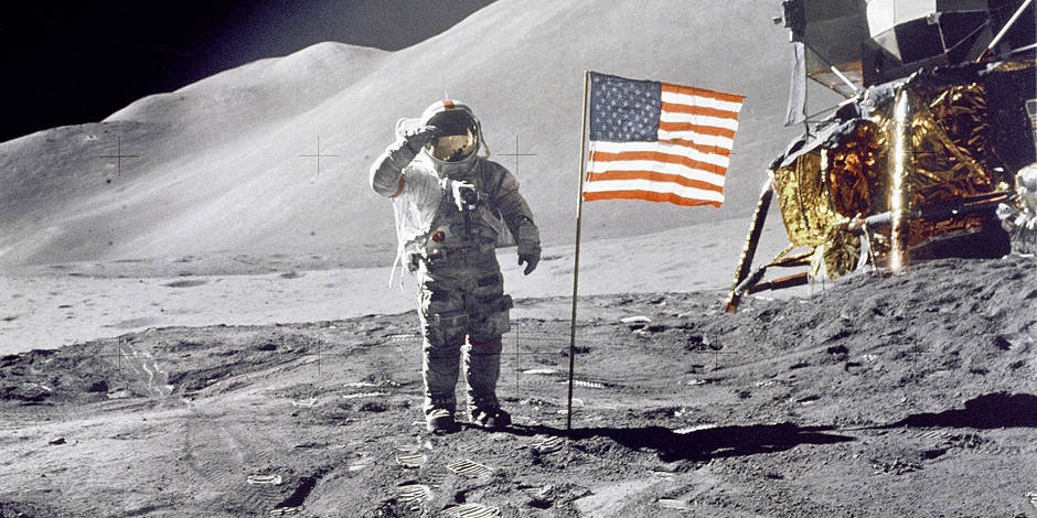 "Astronaut David R. Scott, commander, gives a military salute while standing beside the deployed U.S. flag during the Apollo 15 lunar surface extravehicular activity (EVA) at the Hadley-Apennine landing site. The flag was deployed toward the end of EVA-2. The Lunar Module ""Falcon"" is partially visible on the right. Hadley Delta in the background rises approximately 4,000 meters (about 13,124 feet) above the plain. The base of the mountain is approximately 5 kilometers (about 3 statute miles) away. This photograph was taken by Astronaut James B. Irwin, Lunar Module pilot. August 1, 1971 Reporters / All Access"