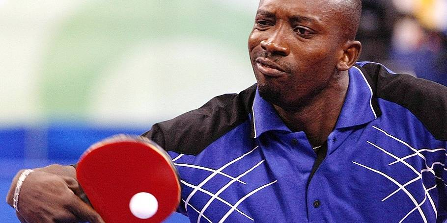 epa01458409 Nigeria's Segun Toriola returns the ball to Belgium's Jean-Michel Saive (unseen) during their Men's singles second round table tennis competition match of the Beijing 2008 Olympic Games at the Peking University Gymnasium Beijing, China, 20 August 2008. EPA/RUNGROJ YONGRIT