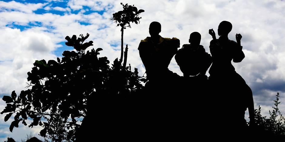 silhouette of three boys sitting on a rock; kampala uganda africa
