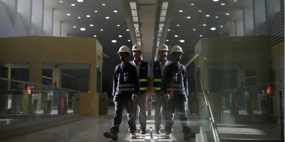 Workers walk at the new subway station in Barra da Tijuca neighborhood, which is part of the Rio de Janeiro's metro line 4 under construction to connect Barra da Tijuca and Ipanema neighborhoods in Rio de Janeiro