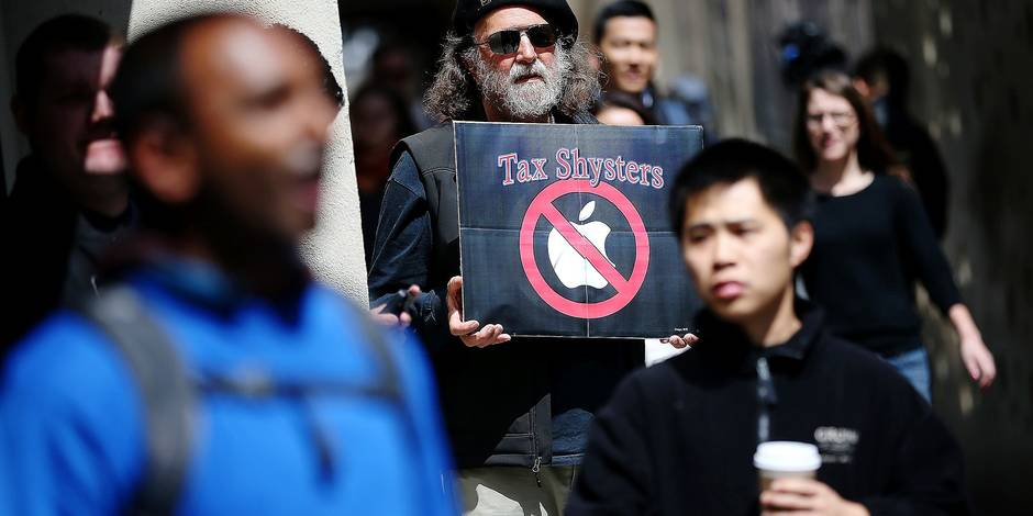 "(FILES) This file photo taken on April 15, 2014 shows a protester holding a sign during a demonstration outside of an Apple Store on April 15, 2014 in San Francisco, California. The European Union on August 30, 2016, said US tech giant Apple must repay a record 13 billion euros ($14.3 billion) in back taxes after ruling that a series of Irish sweetheart tax deals were illegal. ""The European Commission has concluded that Ireland granted undue tax benefits of up to 13 billion euros to Apple. This is illegal under EU state aid rules because it allowed Apple to pay substantially less tax than other businesses. Ireland must now recover the illegal aid,"" a Commission statement said. / AFP PHOTO / GETTY IMAGES NORTH AMERICA / JUSTIN SULLIVAN"