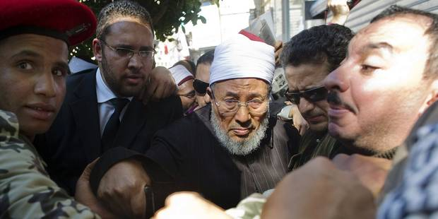 Sheik Youssef al-Qaradawi is protected by soldiers and people as he leaves Cairo's Tahrir Square after delivering the Friday prayer sermon on February 18, 2011 where hundreds of thousands of Egyptians massed to celebrate the fall of strongman Hosni Mubarak. The Qatar-based influential cleric urged Arab leaders to listen to their people and acknowledge their region has changed. AFP PHOTO/PEDRO UGARTE / AFP PHOTO / PEDRO UGARTE