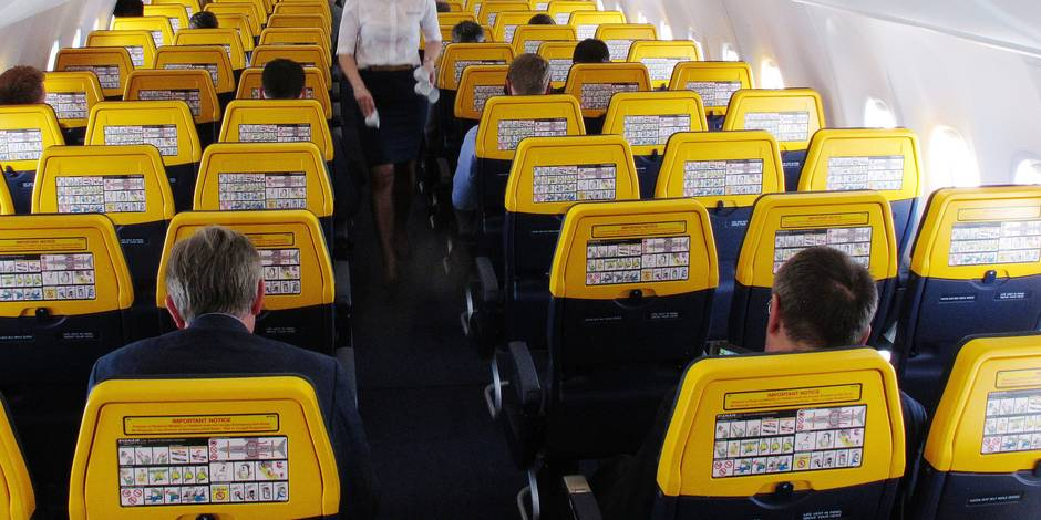 FILE- In this Tuesday, April 12, 2016 file photo, an attendant collects rubbish on a Ryanair media flight from Dublin to Gatwick Airport, London. Ryanair issued a statement Monday, Aug. 14, 2017, calling on British airports to take steps to curb alcohol sales following sharp increases in the number of incidents involving disruptive passengers. (AP Photo/Shawn Pogatchnik, File)