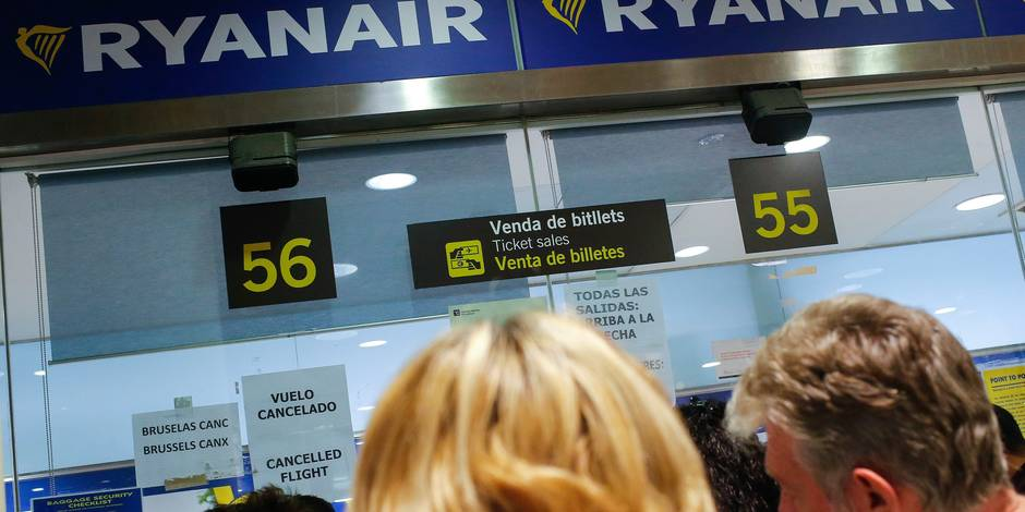 Travellers gather at Ryanair helping desk at Barcelona El Prat airport after the Brussels attacks, in Barcelona on March 22, 2016. Europe froze air and rail links to Brussels as the authorities tightened security in alarm over a series of deadly bomb blasts that ripped through the Belgian capital's airport and a city-centre metro station. / AFP PHOTO / PAU BARRENA