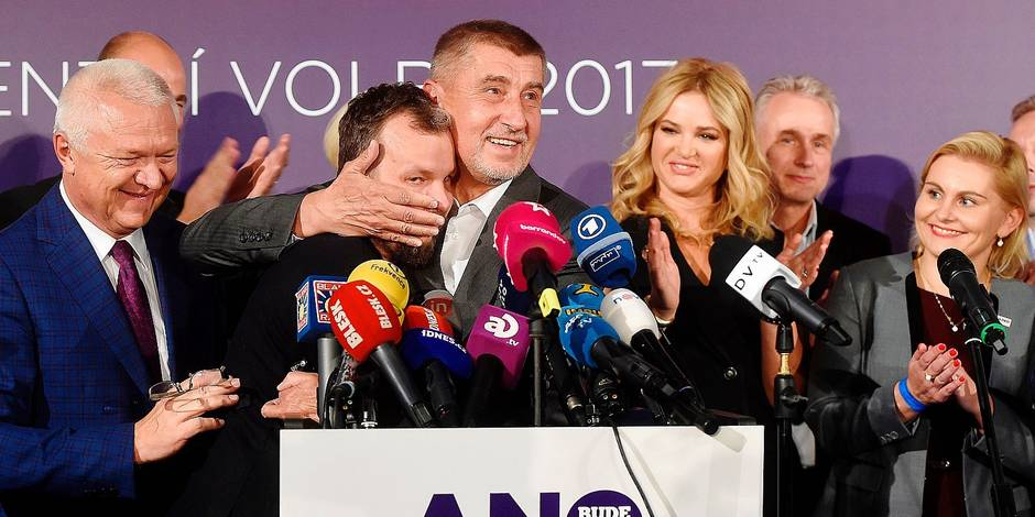"""Czech billionaire Andrej Babis (C,R), chairman of the ANO movement (YES) kisses Marek Prchal, PR manager of ANO for social media at ANO headquarter after Czech elections on October 21, 2017 in Prague. The party of billionaire populist Andrej Babis, The """"Czech Trump"""", took an early lead in the Czech Republic's general election followed by a far-right anti-EU party, partial results showed. / AFP PHOTO / MICHAL CIZEK"""