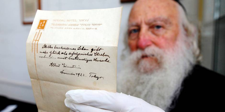 (FILES) This file photo taken on October 19, 2017 shows an Ultra-Orthodox Jewish man displaying one of two notes written by Albert Einstein, in 1922, on hotel stationary from the Imperial Hotel in Tokyo Japan, at the Winner's auction house in Jerusalem. The note that Albert Einstein gave to a courier in Tokyo briefly describing his theory on happy living sold at auction in Jerusalem on October 24, 2017 for $1.56 million, the auction house said. / AFP PHOTO / MENAHEM KAHANA