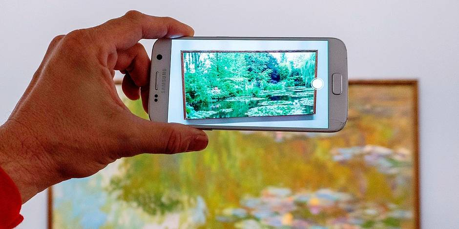 """A visitor is looking at an animation as he points his smartphone at French painter Claude Monet's painting """"Water Lilies"""" using the Artvive app at Albertina Gallery in Vienna, Austria on November 21, 2017. Albertina gallery unveiled 'an augmented reality' app that brings to life paintings by the likes of Monet,Picasso and Degas. / AFP PHOTO / JOE KLAMAR / RESTRICTED TO EDITORIAL USE - MANDATORY MENTION OF THE ARTIST UPON PUBLICATION - TO ILLUSTRATE THE EVENT AS SPECIFIED IN THE CAPTION"""