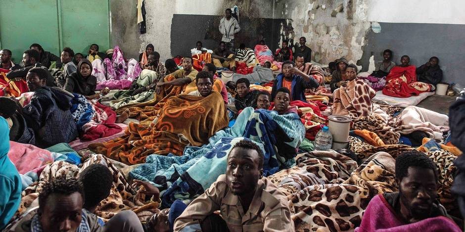A picture taken on November 27, 2017 shows African migrants sitting in a packed room with their beds and blankets, at the Tariq Al-Matar detention centre on the outskirts of the Libyan capital Tripoli. / AFP PHOTO / TAHA JAWASHI