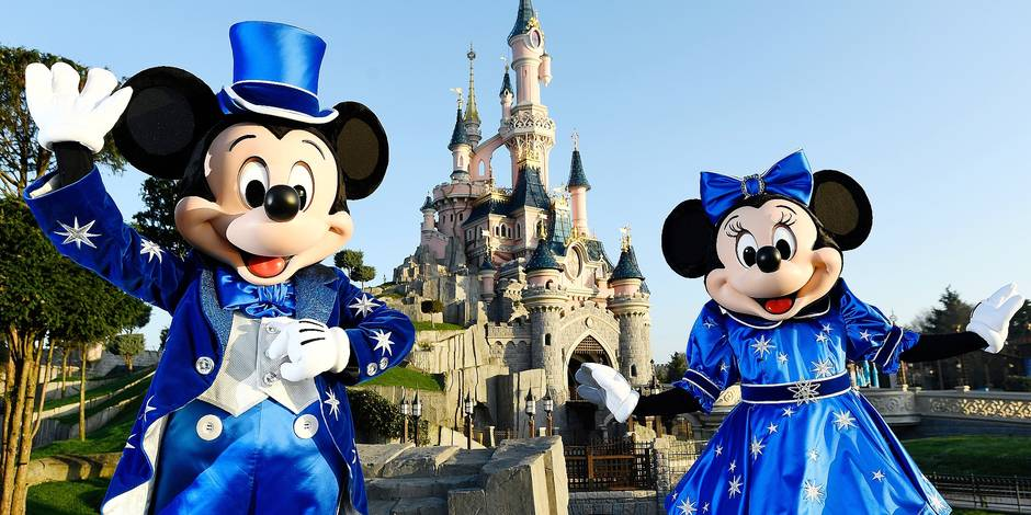Disney characters Mickey and Mini mouse pose in front of the Sleeping Beauty Castle to mark the 25th anniversary of Disneyland - originally Euro Disney Resort - on March 16, 2017 in Marne-La-Vallee, east of the French capital Paris. The 25th anniversary celebrations will begin on March 26, 2017 with parades, various shows and a firework's display. / AFP PHOTO / BERTRAND GUAY