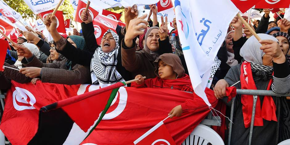 Tunisians wave their national flag and the flag of the Ennahda Islamist party as they gather on Habib Bourguiba Avenue in Tunis on January 14, 2018 to mark the seven year anniversary since the uprising that launched the Arab Spring. A wave of peaceful protests and night-time unrest hit cities and towns across the country this past week, after hikes in value-added tax and social security contributions introduced in early January. / AFP PHOTO / FETHI BELAID
