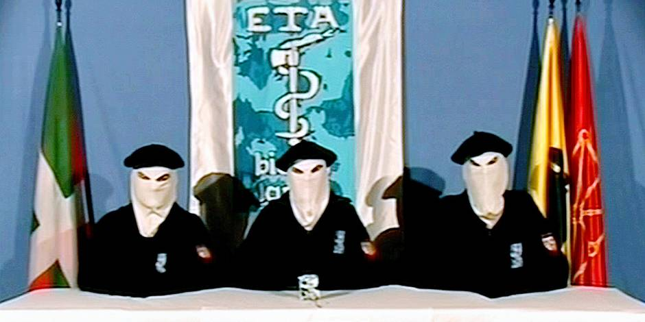FILE - This video frame, seen in this March 22, 2006 file photo, which was released by the Basque separatist group ETA, shows three unidentified people with their faces covered, wearing Basque berets and seated at a table in front of an ETA flag with a Basque Country symbol in foreground. The Basque daily Gara says the armed group ETA has issued a statement Thursday Oct. 20, 2011 saying it is ending its armed campaign and calls on Spain and France to open talks. (AP Photo/Basque Television, File)